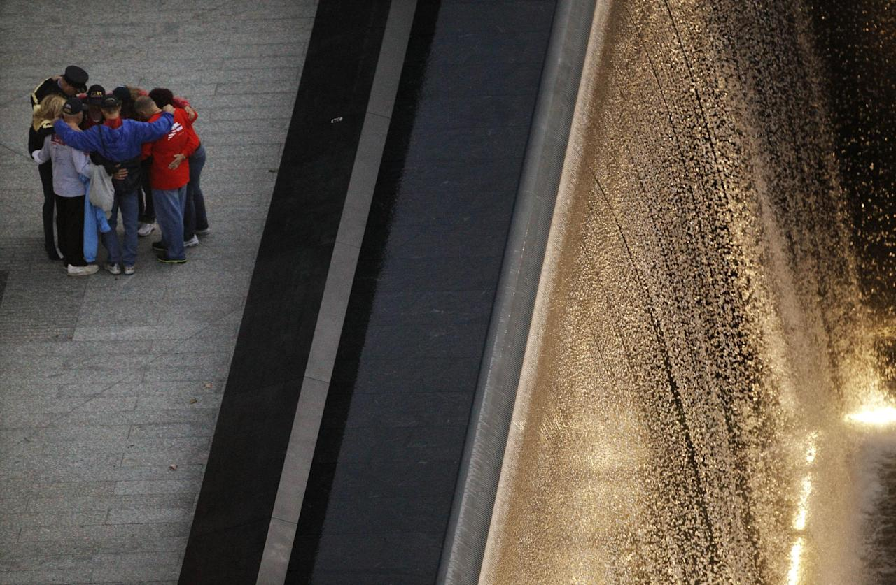 People pause by the waterfall pool at the National September 11 Memorial before a planned ceremony marking the 10th anniversary of the attacks at the World Trade Center site, Sunday, Sept. 11, 2011, in New York. (AP Photo/Matt Rourke)