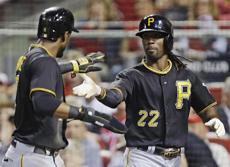 Pittsburgh Pirates' Andrew McCutchen (22) and Starling Marte slap hands with each other after they scored on a hit by Marlon Byrd off Cincinnati Reds starting pitcher Homer Bailey during the third inning of a baseball game, Friday, Sept. 27, 2013, in Cincinnati. (AP Photo/Al Behrman)