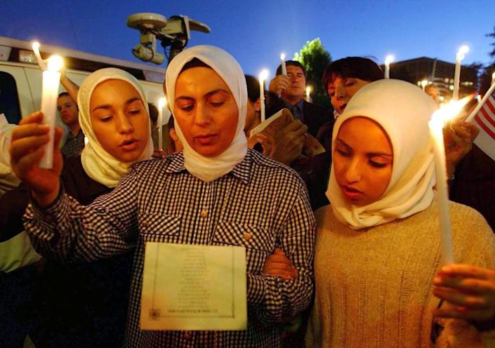 Lena Alfi, her mother Manal Alfi and Heba Hathout sing God Bless America on 13 September 2001 in Pasadena, California, at an interfaith memorial service for victims of the 9/11 attacks.