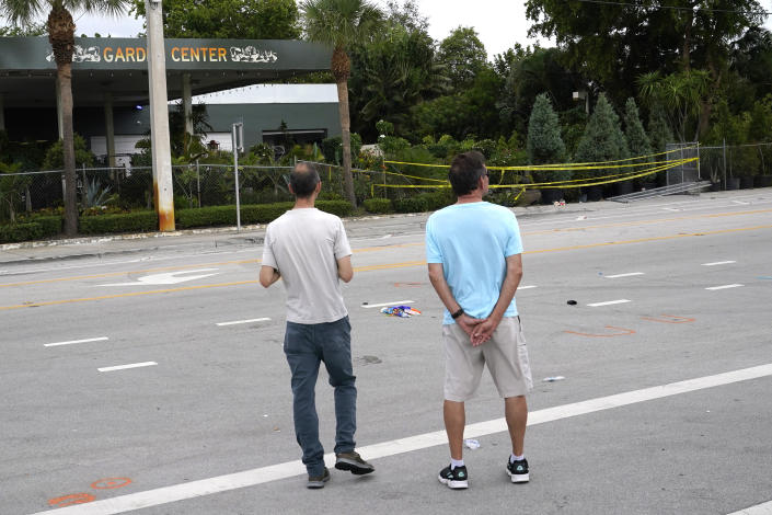 People look at the site where a driver slammed into spectators at the start of a Pride parade Saturday evening, killing one man and seriously injuring another, Sunday, June 20, 2021, in Fort Lauderdale, Fla. Officials said the crash was an accident, but it initially drew speculation that it was a hate crime directed at the gay community. The driver and victims were all members of the Fort Lauderdale Gay Men's Chorus, who were participating in the Wilton Manors Stonewall Pride Parade. (AP Photo/Lynne Sladky)