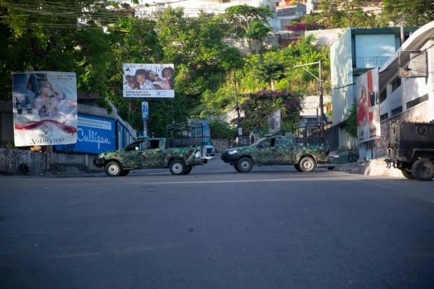 Military vehicles block the entrance to Pétion-Ville, the Port-au-Prince neighbourhood where Haitian President Jovenel Moïse was assassinated in his home early on Wednesday.  (Joseph Odelyn/The Associated Press - image credit)