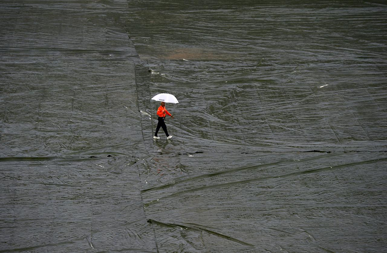 Sri Lankan cricket umpire Raveendra Wimalasiri walks holds an umbrella as he walks over the tarp-covered ground as rain stops play during the second One Day International (ODI) cricket match between Sri Lanka and New Zealand at the Suriyawewa Mahinda Rajapakse International Cricket Stadium in the southern district of Hambantota on November 12, 2013. AFP PHOTO/ LAKRUWAN WANNIARACHCHI        (Photo credit should read LAKRUWAN WANNIARACHCHI/AFP/Getty Images)