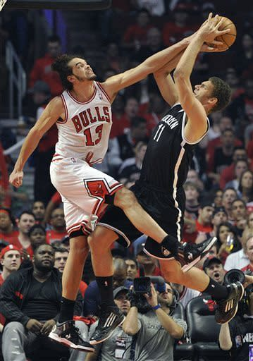 Chicago Bulls' Joakim Noah (13) blocks the shot of the Brooklyn Nets' Brook Lopez (11) during the first half in Game 4 of their first-round NBA basketball playoff series Saturday, April 27, 2013, in Chicago. (AP Photo/Jim Prisching)