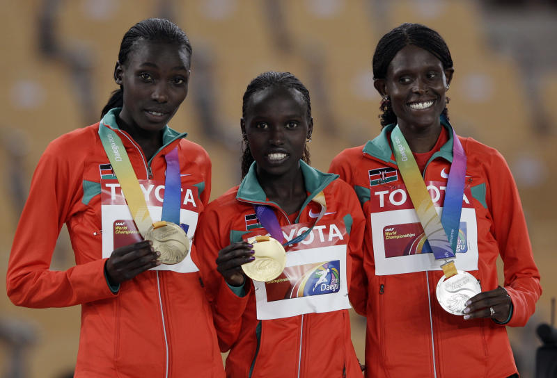 Kenya's Vivian Jepkemoi Cheruiyot, gold medalist, center, is flanked by her compatriots  Sally Kipyego, silver and left,  and Linet Chepkwemoi Masai, bronze, on the podium for  the Women's 10,000m  at the World Athletics Championships in Daegu, South Korea, Saturday, Aug. 27, 2011. (AP Photo/David J. Phillip)