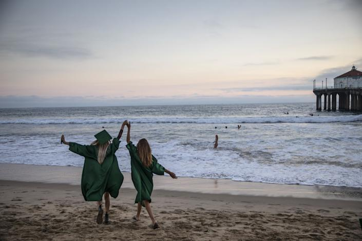 Two girls in graduation gowns walk on the sand near a pier, their clasped hands upraised.