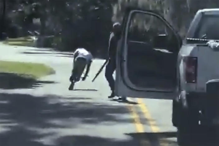 ADDS THAT THE AP HAS NOT BEEN ABLE TO VERIFY THE SOURCE OF THE VIDEO - This image from video posted on Twitter Tuesday, May 5, 2020, purports to show Ahmaud Arbery stumbling and falling to the ground after being shot as Travis McMichael stands by holding a shotgun in a neighborhood outside Brunswick, Ga., on Feb. 23, 2020. The AP has not been able to verify the source of the video. (Twitter via AP)