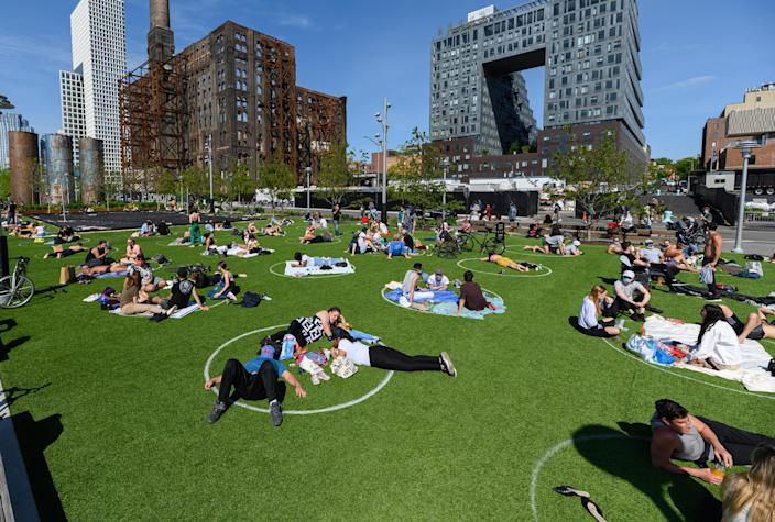 NEW YORK, NEW YORK - MAY 17: People practice social distancing in white circles in Domino Park in Williamsburg during the coronavirus pandemic. (Photo by Noam Galai/Getty Images)