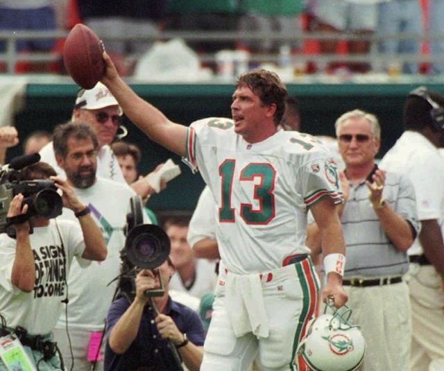 Miami Dolphins quarterback Dan Marino salutes the fans in this 1995 game against the Patriots, but not for his first career reception. (AP)