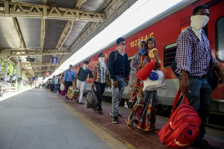 Indian migrant workers queue to board a special train from the outskirts of Ahmedabad in Gujarat to Agra in Uttar Pradesh state, while regular public transport is still barred under coronavirus restrictions