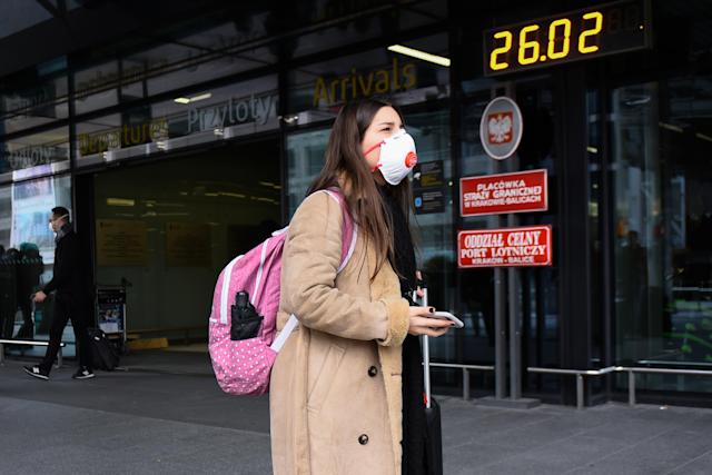 A passenger is pictured wearing a mask after landing at Krakow International Airport on 26 February. Poland has no confirmed cases. (Getty Images)