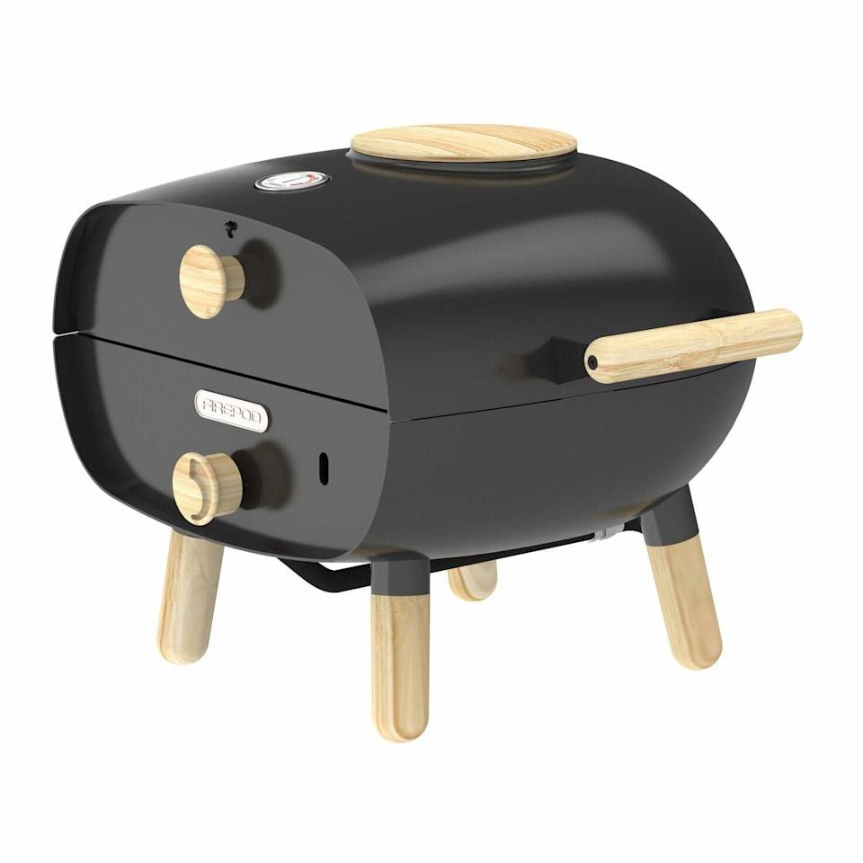 """For a more simple, classic profile, the Firepod makes us think of what a pizza oven by <a href=""""https://www.muji.com/us/"""" rel=""""nofollow"""">Muji</a> would look like. The oven has a high-temperature enamel coating and eco-friendly hardwood elements, and if the black is too understated, it is available in deep purple, bright red, or peppy teal. The reversible baking stones are ideal if Dad is cooking for those with food allergies or extreme pickiness. <a href=""""https://www.thefirepod.com/products/firepod-black"""" rel=""""nofollow"""">SHOP NOW</a>: Portable Multi-Functional Pizza Oven by Firepod, $399, thefirepod.com"""