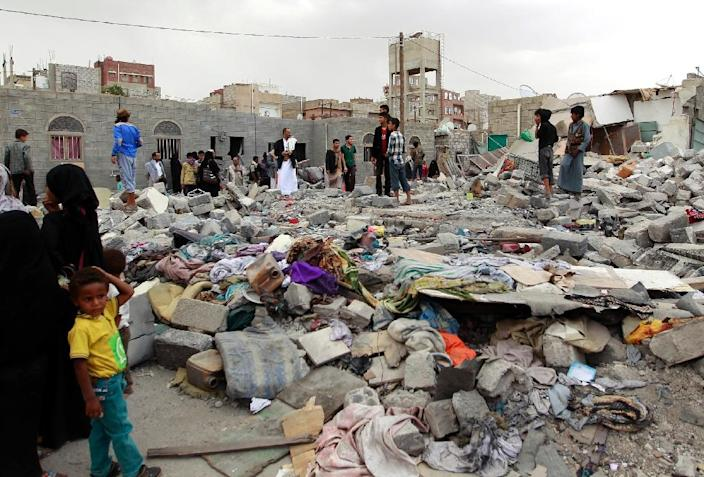 Yemenis stand amid the ruins of buildings destroyed in an air-strike by the Saudi-led coalition on the capital Sanaa on July 13, 2015 (AFP Photo/Mohammed Huwais)