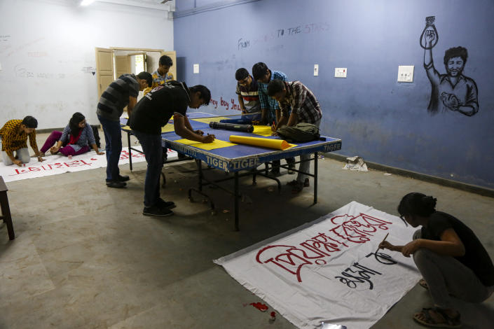 University students paint posters and banners demanding justice in the case of a veterinarian who was gang-raped and killed last week prior to a protest rally in Kolkata, India, Monday, Dec. 2, 2019. The burned body of the 27-year-old woman was found Thursday morning by a passer-by in an underpass in the southern city of Hyderabad after she went missing the previous night. (AP Photo/Bikas Das)