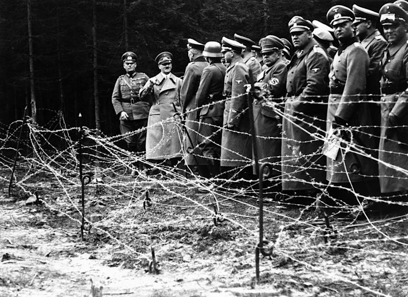 "FILE- In this Oct. 6, 1938, file photo, Adolf Hitler, second from left, stands in front of the barbed wire fortifications at Kreuzbuche, Germany after German troops advanced and occupied the second zone of Sudetenland. The book, ""Human Rights After Hitler"" by British academic Dan Plesch, says Hitler was put on the United Nations War Crimes Commission's first list of war criminals in December 1944, but only after extensive debate and formal charges brought by Czechoslovakia. Plesch, who led the campaign for open access to the commission's archive, told The Associated Press on Tuesday, April 18, 2017, that the documents show ""the allies were prepared to indict Hitler as head of state, and this overturns a large part of what we thought we knew about him."" (AP Photo, File)"