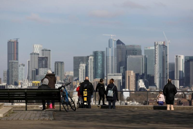 FILE PHOTO: People look out onto the Canary Wharf district as they walk through Greenwich Park in London