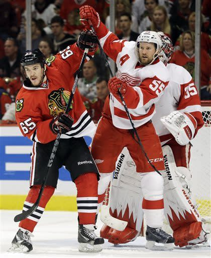Chicago Blackhawks' Andrew Shaw (65) and Detroit Red Wings' Niklas Kronwall (55) battle as they wait for the puck during the second period of Game 5 of the NHL hockey Stanley Cup playoffs Western Conference semifinals in Chicago, Saturday, May 25, 2013. The Blackhawks won 4-1. (AP Photo/Nam Y. Huh)