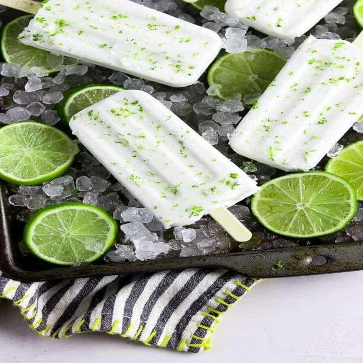 Green and white ice pops surrounded by cut slices of lime