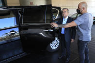 Escorted by his bodyguard, fugitive ex-auto magnate Carlos Ghosn, center, stands next to a Nissan SUV, as he leaves after an interview with the Associated Press, in Dbayeh, north of Beirut, Lebanon, Tuesday, May 25, 2021. The embattled former chairman of the Renault-Nissan-Mitsubishi alliance dissected his legal troubles in Japan, France and the Netherlands, detailed how he plotted his brazen escape from Osaka, and reflected on his new reality in crisis-hit Lebanon, where he is stuck for the foreseeable future. (AP Photo/Hussein Malla)