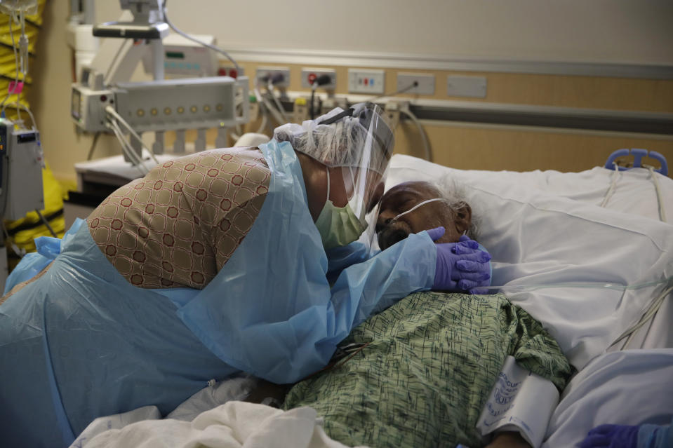 """Romelia Navarro, 64, weeps while hugging her husband, Antonio, in his final moments in a COVID-19 unit at St. Jude Medical Center in Fullerton, Calif., July 31, 2020. Photographer Jae C. Hong said even though he had the family's consent to be there, he struggled to shoot the intimate scene, feeling uneasy to even pick up his camera and document the end of someone's life. """"Capturing someone else's painful emotion never gets easier,"""" Hong said. """"What I saw that day still haunts me from time to time."""" (AP Photo/Jae C. Hong)"""