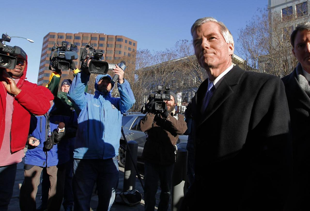 Former Va. Governor Bob McDonnell, right, surrounded by news cameras, enters U.S. District Court in Richmond, Va. for his and his wife Maureen's bond hearing and arraignment on Friday, Jan. 24, 2014 on federal corruption charges. The McDonnells, flanked by their children, did not comment as they entered the courthouse. (AP Photo/ Richmond Times-Dispatch, Dean Hoffmeyer)