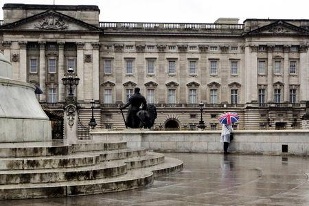 Tourist stands in the rain outside Buckingham Palace in London