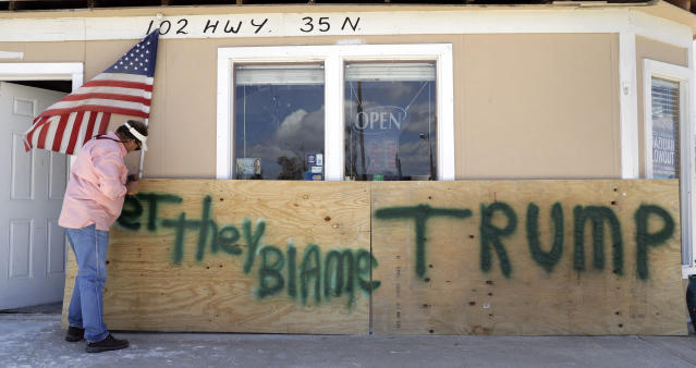 "<p>John Murray attaches a U.S. flag to a sign reading ""Bet They Blame Trump"" at his business damaged in the wake of Hurricane Harvey, Tuesday, Aug. 29, 2017, in Rockport, Texas. Murray created the sign in hopes President Donald Trump would visit Rockport during his Texas visit, but he did not expect him to make the trip. (Photo: Photo: Eric Gay/AP) </p>"