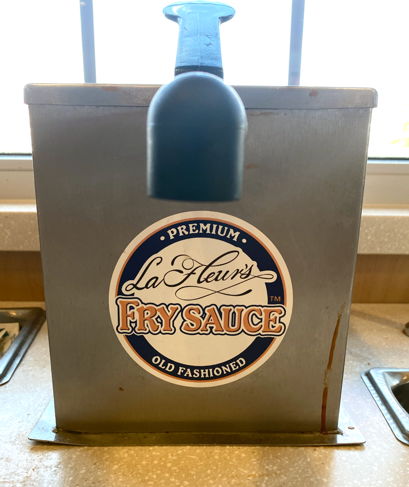 A metal box with a pump and a label that says La Fleur's premium, old fashion fry sauce