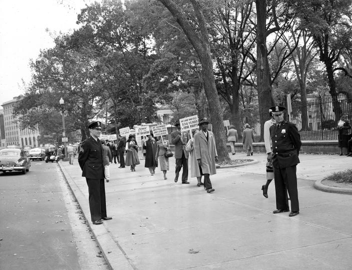 Officers stands by as black religious leaders from Chicago demonstrate outside the White House in Washington against the murder of 14-year-old Chicagoan boy Emmett Louis Till, on October 24, 1955.