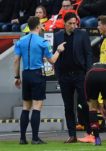 Referee Felix Zwayer (L) talks to Leverkusen's head coach Roger Schmidt during a German first division Bundesliga football match on February 21, 2016 (AFP Photo/Patrik Stollarz)