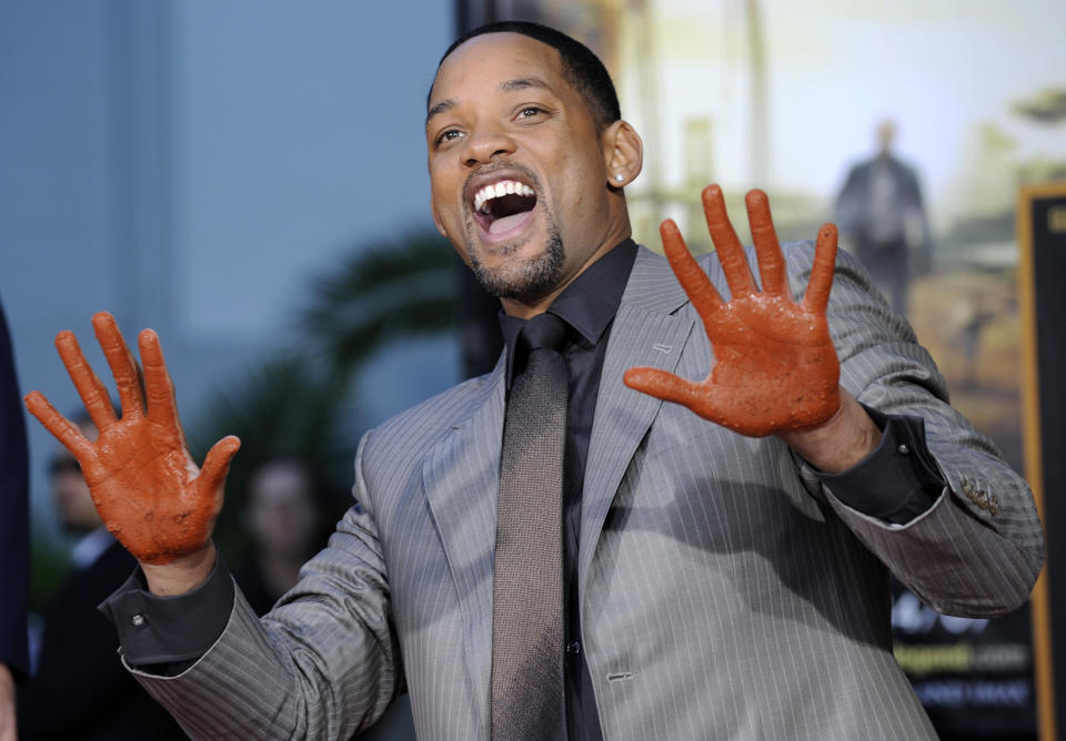 Actor Will Smith shows off his hands after putting them in cement during a ceremony at Grauman's Chinese Theatre in Los Angeles, December 10, 2007. REUTERS/Chris Pizzello (UNITED STATES)