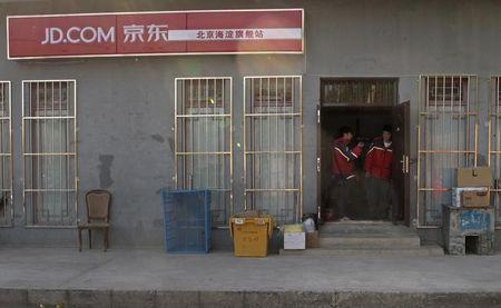 Two Jingdong, also known as JD.com, couriers chat at the entrance to the company's Haidian district delivery station in Beijing