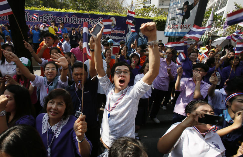 A supporter cheers on a passing anti-government march in Bangkok Thursday, Jan. 30, 2014. Thailand's government announced Tuesday it will go ahead with an election this weekend despite an opposition boycott, months of street protests and the likelihood of more violence in the country's political crisis. (AP Photo/Wally Santana)
