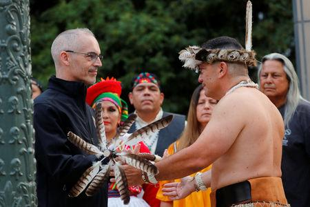 """Los Angeles City Council member Mitch O'Farrell (L) is presented a running staff by Kevin Nunez of the Gabrielino-Tongva tribe during a sunrise ceremony after Los Angeles City Council voted to establish the second Monday in October as """"Indigenous People's Day"""", replacing Columbus Day, in Los Angeles, California, U.S., October 8, 2018. REUTERS/Mike Blake"""
