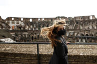A woman visits the Rome's ancient Colosseum after its reopening Monday, Feb. 1, 2021, in a partial lifting of restriction measures aimed at containing the spread of COVID-19. Italy has eased its coronavirus restrictions Monday for most of the country downgrading Lazio and other regions from medium-risk orange zones to lower-risk yellow zones. (Cecilia Fabiano /LaPresse via AP)