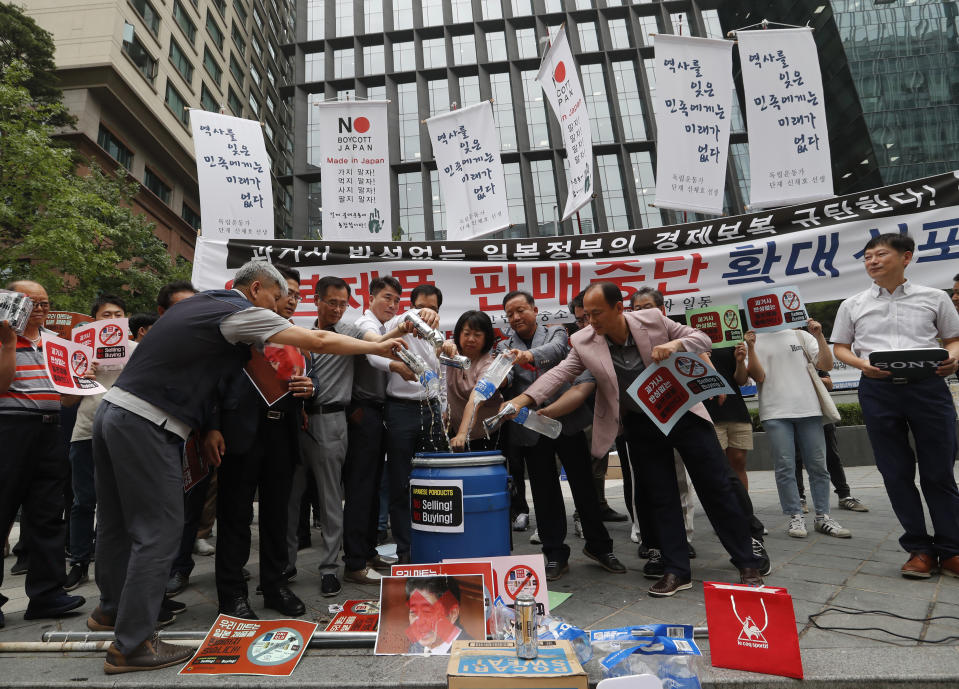 "South Korean small and medium-sized business owners pour beers and drinking waters from Japanese brands into a trash can during a rally calling for a boycott of Japanese products in front of the Japanese embassy in Seoul, South Korea, Monday, July 15, 2019. South Korea and Japan last Friday, July 12, failed to immediately resolve their dispute over Japanese export restrictions that could hurt South Korean technology companies, as Seoul called for an investigation by the United Nations or another international body. The signs read: ""Our supermarket does not sell Japanese products."" (AP Photo/Ahn Young-joon)"