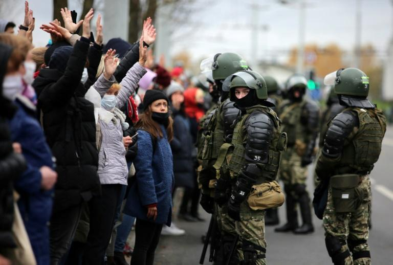 Belarus law enforcement officers block anti-government protesters during a march of opposition supporters from central Minsk to a site of Stalin-era executions just outside the capital on November 1, 2020