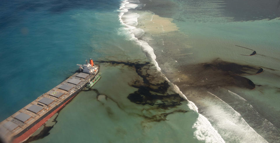 """This photo provided by the French Defense Ministry shows oil leaking from the MV Wakashio, a bulk carrier ship that recently ran aground off the southeast coast of Mauritius,, Sunday Aug.9, 2020. The Indian Ocean island of Mauritius has declared a """"state of environmental emergency"""" after the Japanese-owned ship that ran aground offshore days ago began spilling tons of fuel. (Gwendoline Defente/EMAE via AP)"""