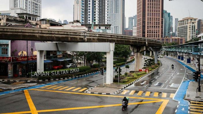 A food delivery rider is seen riding along an empty street in downtown Kuala Lumpur. Malaysia government starts to further tighten the movement control and imposes lockdown in state of Selangor and parts of Kuala Lumpur.