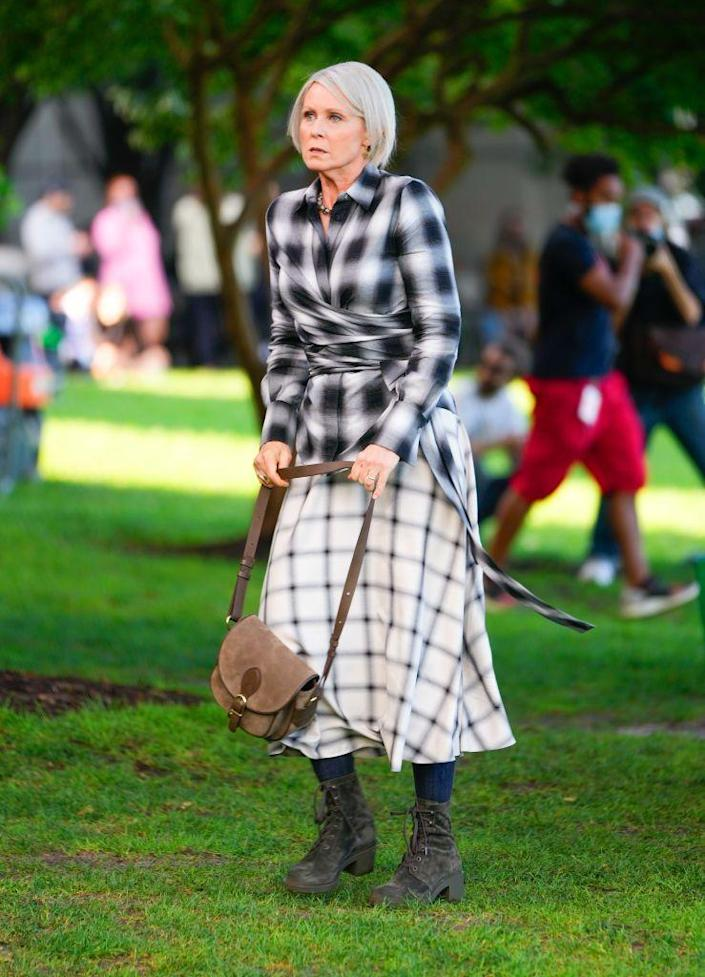 <p>In a dark-neutral ensemble, Cynthia Nixon wore Altuzarra's wrap-waist Mckenna shirt along with Akris's windowpane check midi skirt. She paired the look with block-heel suede combat boots by Gianvito Rossi and a leather flat bag by Gerard Darel.<br></p>