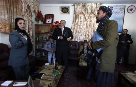 Colonel Jamila Bayaaz (L) talks with Afghans at her office in Kabul January 15, 2014. REUTERS/Mohammad Ismail