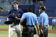 Tampa Bay Rays pitcher Ryan Yarbrough, left, walks off after being checked for foreign substances by umpires Phil Cuzzi, center, and Tom Hallion, right, after Yarbrough was taken out of the game against the Boston Red Sox during the third inning of a baseball game Tuesday, June 22, 2021, in St. Petersburg, Fla. (AP Photo/Chris O'Meara)
