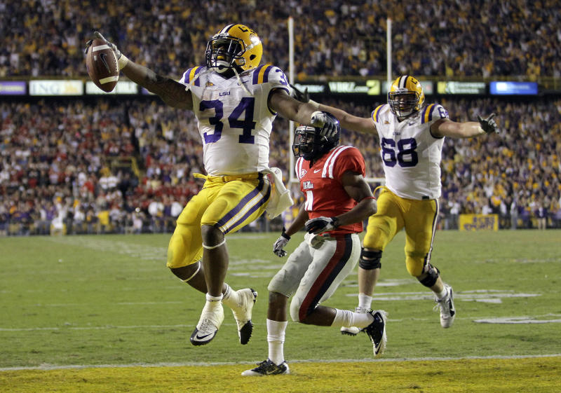 "FILE - In this Nov. 20, 2010, file photo, LSU running back Stevan Ridley (34) celebrates as he scores a touchdown during an NCAA college football game against Mississippi in Baton Rouge, La. A person familiar with Ridley's eligibility status says the Tigers' leading rusher has been cleared to play against Texas A&M in the Cotton Bowl on Friday, Jan. 7. Ridley's eligibility had been in doubt since head coach Les Miles said on Dec. 22 that the running back could miss the game because of an unspecified ""one-time"" academic violation. (AP Photo/Patrick Semansky, File)"