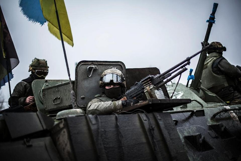 Ukrainian soldiers are seen in an armoured vehicle topped with a Ukrainian flag near the city of Artemivsk before heading to the city of Debaltseve on February 1, 2015 (AFP Photo/Manu Brabo)