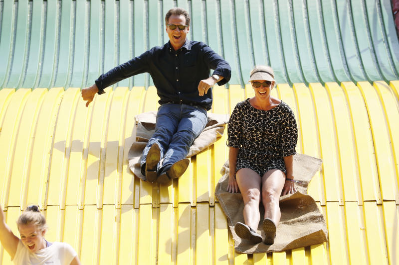 Democratic presidential candidate Montana Gov. Steve Bullock rides down the giant slide with his wife Lisa, right, during a visit to the Iowa State Fair, Thursday, Aug. 8, 2019, in Des Moines, Iowa. (AP Photo/Charlie Neibergall)