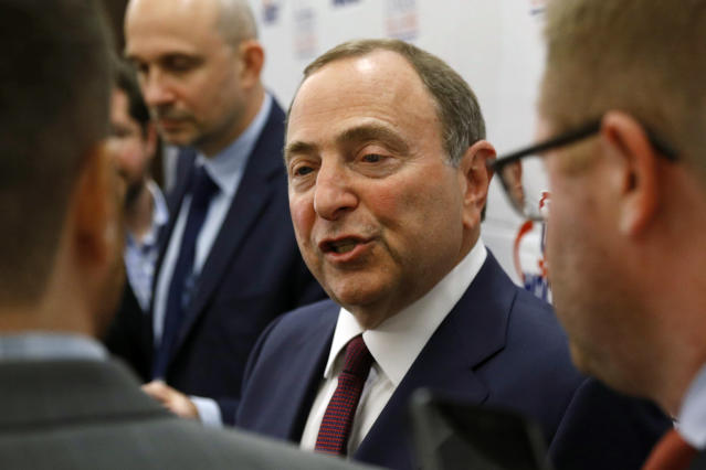 FILE - In this Dec. 12, 2019, file photo, NHL Commissioner Gary Bettman speaks with members of the media before being inducted into the U.S. Hockey Hall of Fame in Washington. The uncertainty raised by coronavirus pandemic leads to experts providing a bleak short-term assessment on the NHL's financial bottom line, with some projecting revenues being cut by almost half. What's unclear is how large the impact might be until it can be determined when fans can resume attending games and if the league is able to complete this season. (AP Photo/Patrick Semansky, File)