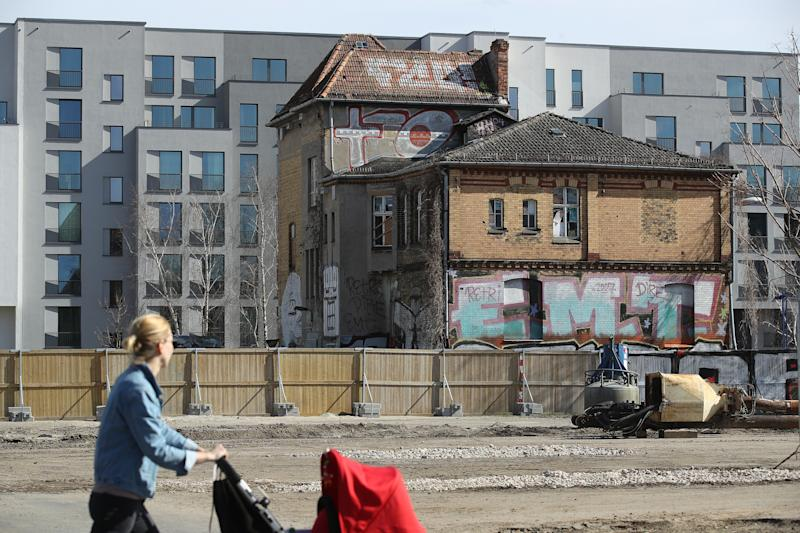 A woman pushes a pram as she walks past a pre-World War II house that stands next to new apartment buildings in a former industrial area on April 4, 2018 in Berlin, Germany. Photo: Sean Gallup/Getty Images