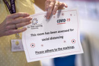 Reception teacher Elizabeth Dockry places signage in a classroom as measures are taken to prevent the transmission of coronavirus before the possible reopening of Lostock Hall Primary school in Poynton near Manchester, England, Wednesday May 20, 2020. (AP Photo/Jon Super)