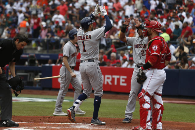Houston Astros' Carlos Correa, center, is congratulated by teammate Michael Brantley as he crosses home after hitting a home run in the second inning of a baseball game against the Los Angeles Angels, in Monterrey, Mexico, Sunday, May 5, 2019. (AP Photo/Rebecca Blackwell)