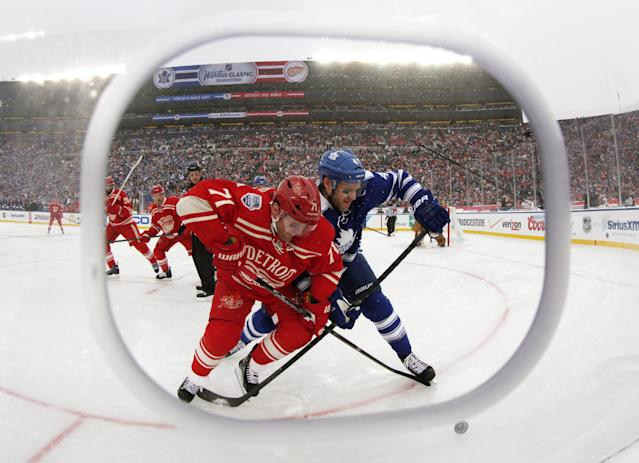 Framed by cutout in the safety glass, Detroit Red Wings right wing Daniel Cleary (71) and Toronto Maple Leafs defenseman Cody Franson (4) battle for the puck during the third period of the Winter Classic outdoor NHL hockey game at Michigan Stadium in Ann Arbor, Mich., Wednesday, Jan. 1, 2014. (AP Photo/Paul Sancya)