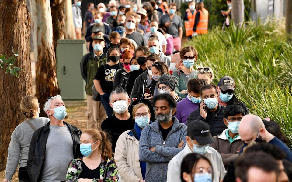 Sydney residents queue outside a vaccination centre as tough new restrictions were applied to the city - AFP